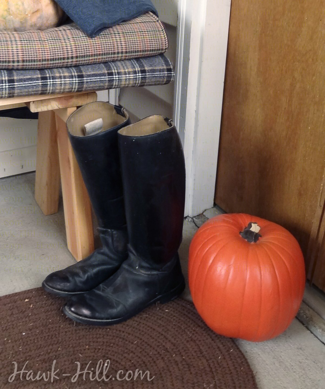 Black boots next to a pumpkin on a porch.
