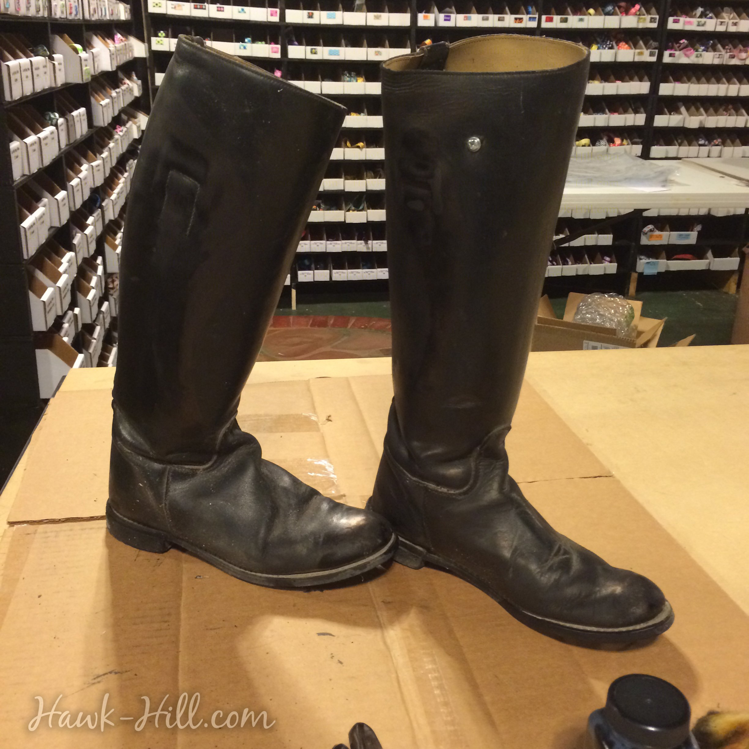 Worn leather riding boots looking new with an application of dye.