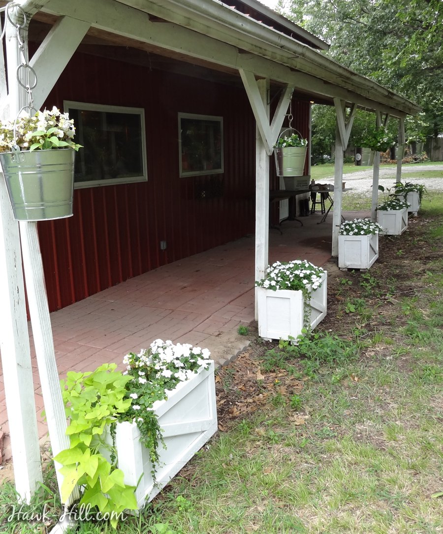 "Ranch style porch with hanging ""baskets"" using buckets and planter boxes"