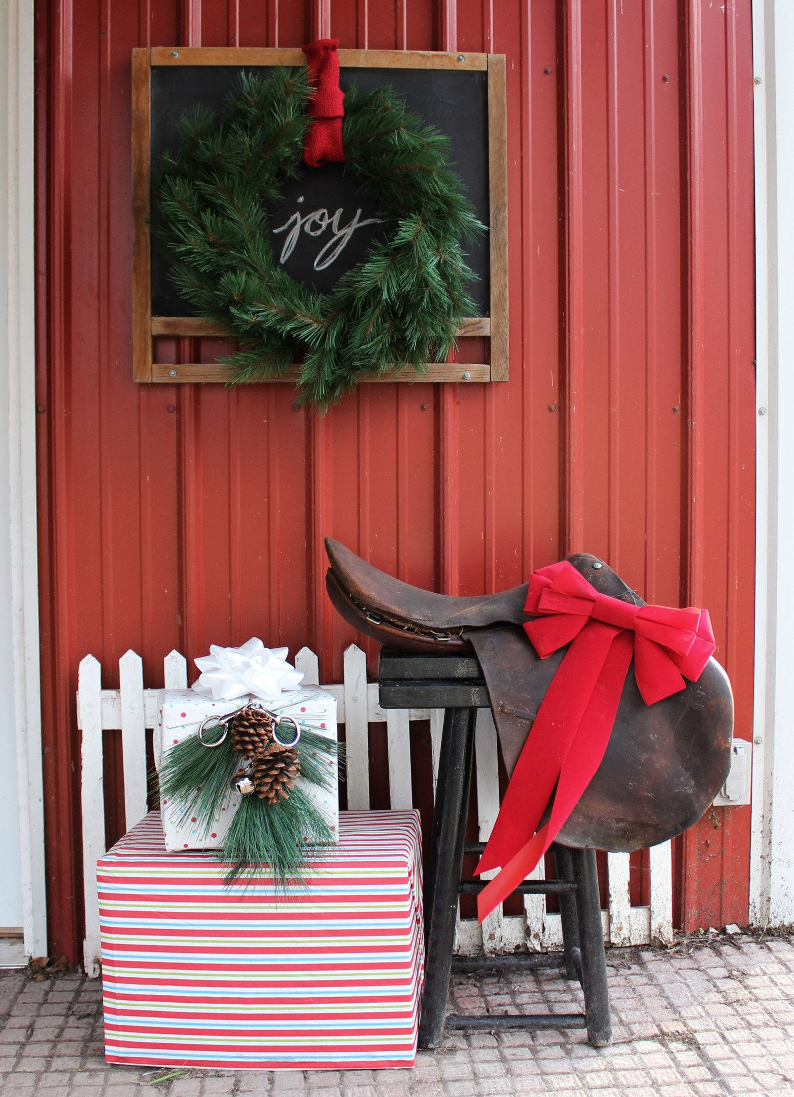 outdoor christmas decorations featuring equestrian english saddle, wrapped gifts, chalkboard, wreaths, silver bells, and snaffle bit