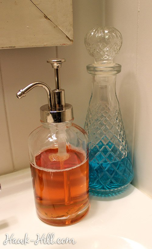 reproduction soap dispenser paired with vintage whiskey decanter of mouthwash