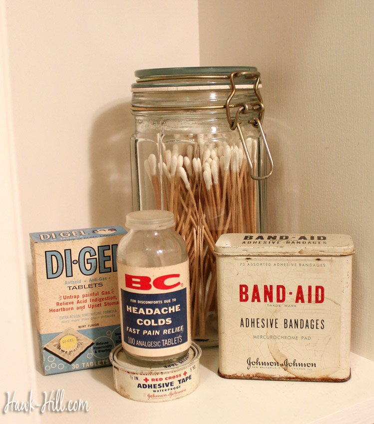 vintage washroom shelf decor- vintage band aid tin, red cross tape, and di-gel