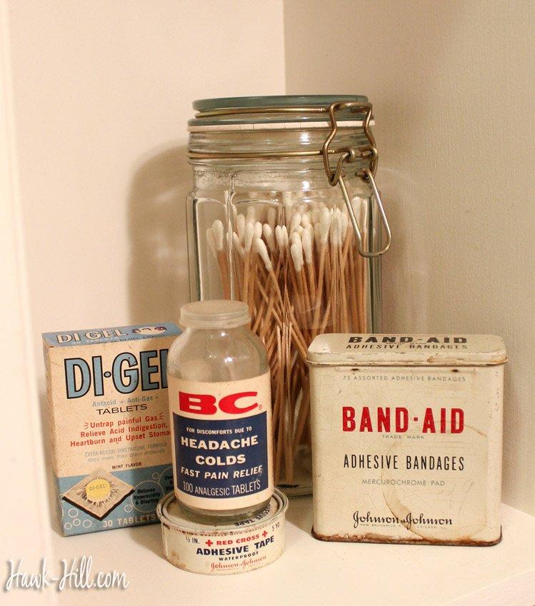 vintage washroom shelf decor- vintage band aid tin, red cross tape, and di-gel
