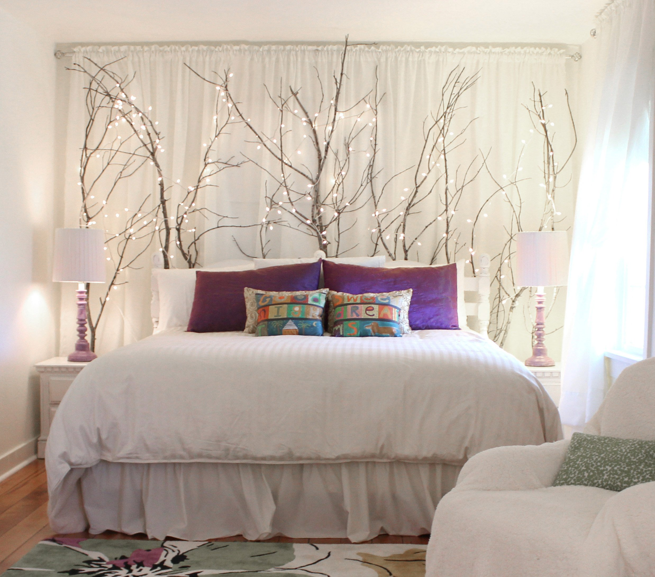 a bed with tree branches decorating the wall behind it and forming a headboard