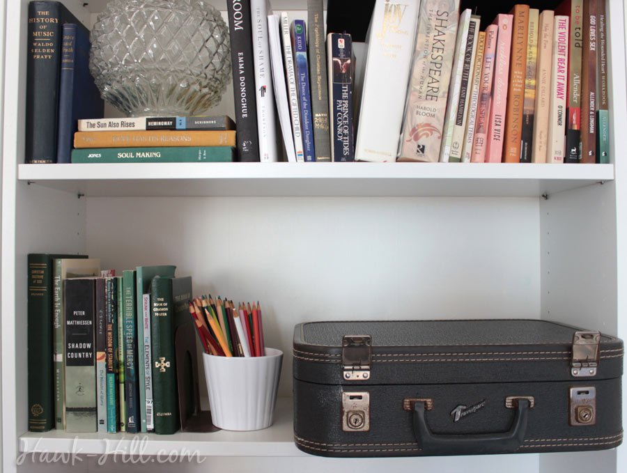 studio apartment organization storage tricks - luggage on bookshelves
