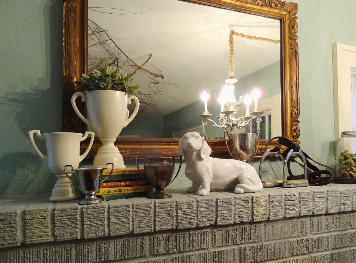 stirrups and trophy cups displayed on an equestrian mantle