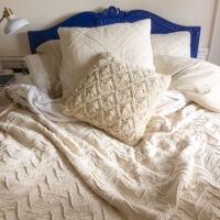 A bed with an ornate blue headboard is made up with a cream colored duvet cover and textured pillows.