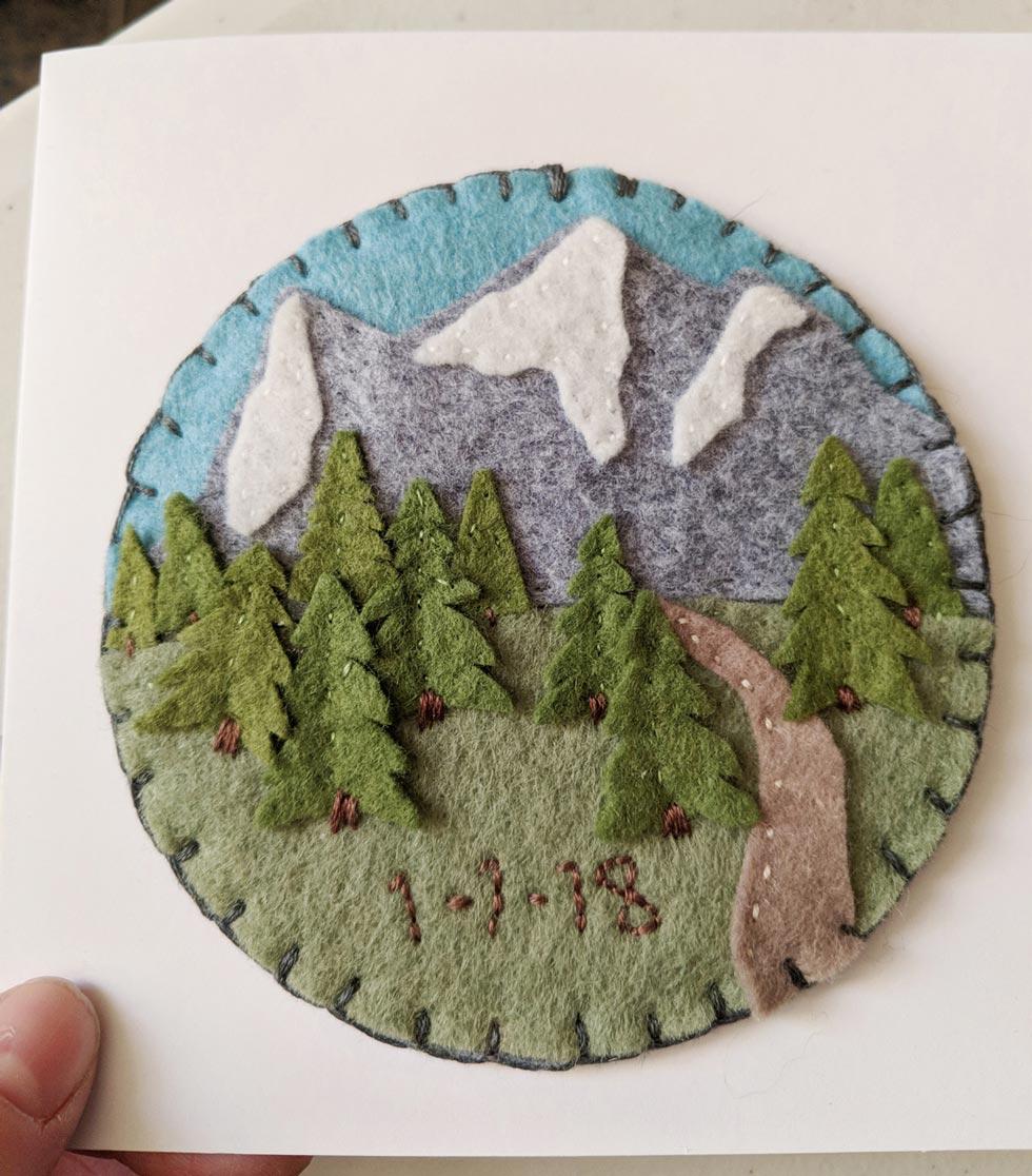 Handmade felt art medallion showing a mountain scene.