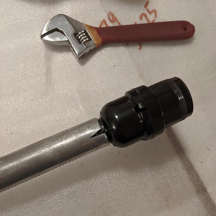 A small cut can be made in the center pipe of the tripod to make the light socket fit