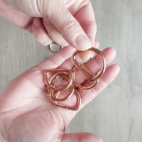 A person's hands hold rose gold D rings.