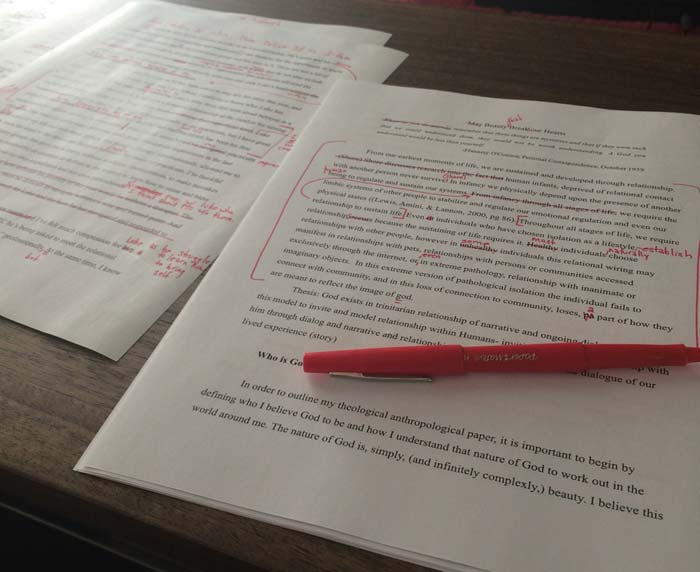 An academic paper printed with red corrections