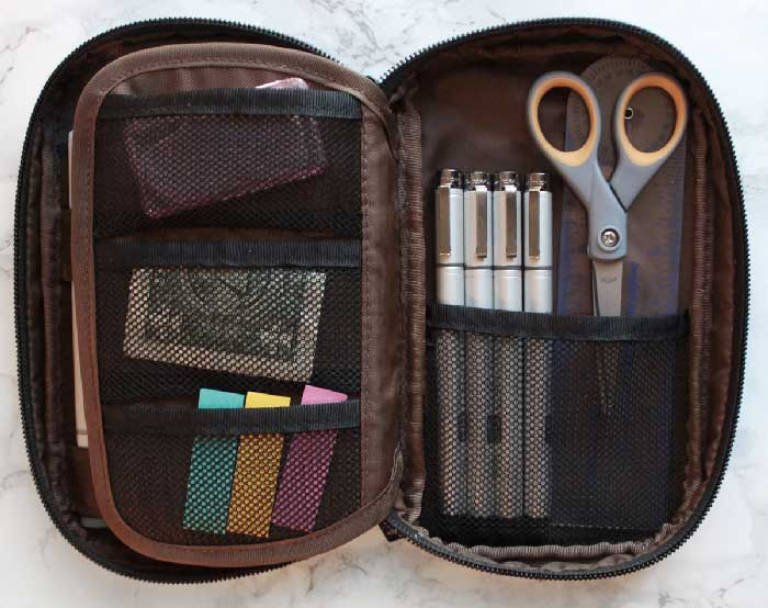 Small scissors, page flags, and liner pens in a pen case sized perfectly for use in class