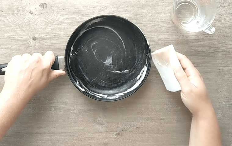 repeat the process until the magic eraser does not discolor when rubbed on the pan
