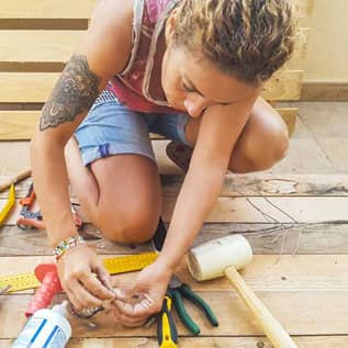 A young adult woman with a tattoo is shown kneeling next to tools and holding a project in her hands.