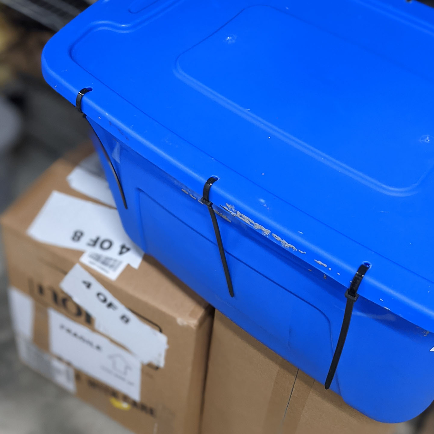 A blue storage tote with heavy duty zip ties sealing the container shut.