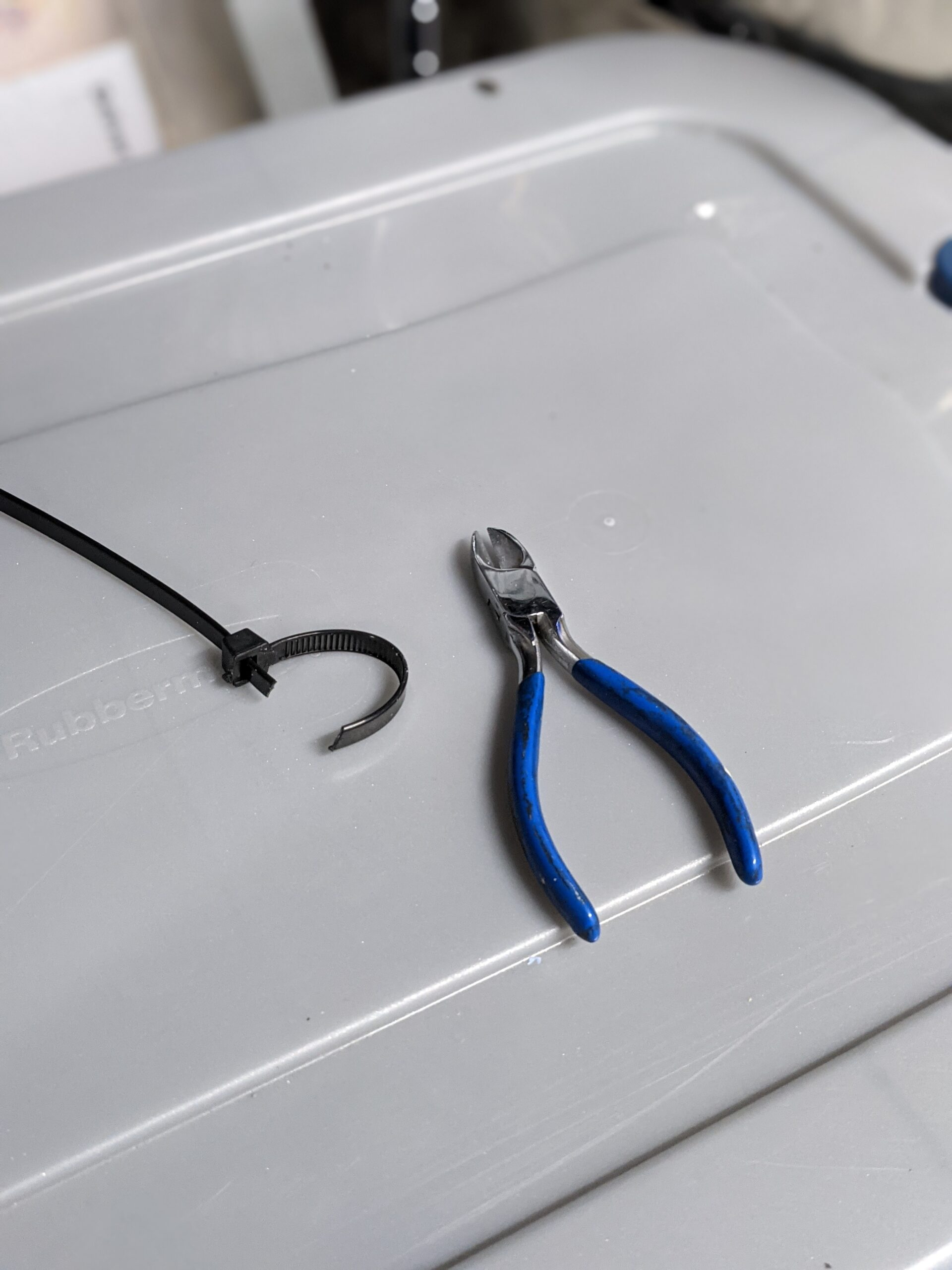 Wire cutter pictured next to a cut heavy duty zip tie, on top of a plastic storage tote.