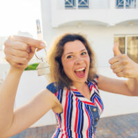 A woman in a striped shirt poses in front of a house with a thumbs up while holding keys in her opposite hand.