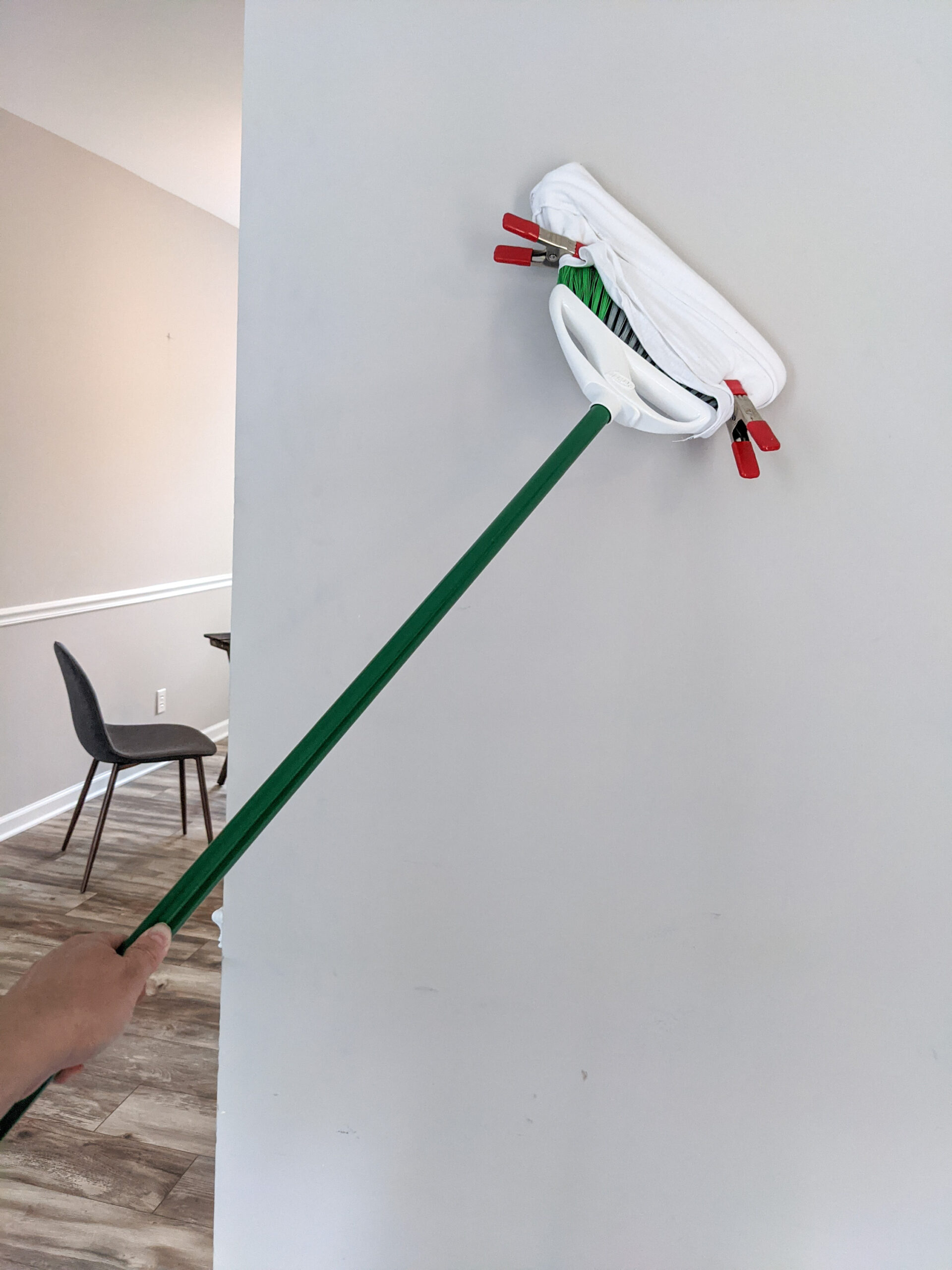 A wall being cleaned with a modified broom.