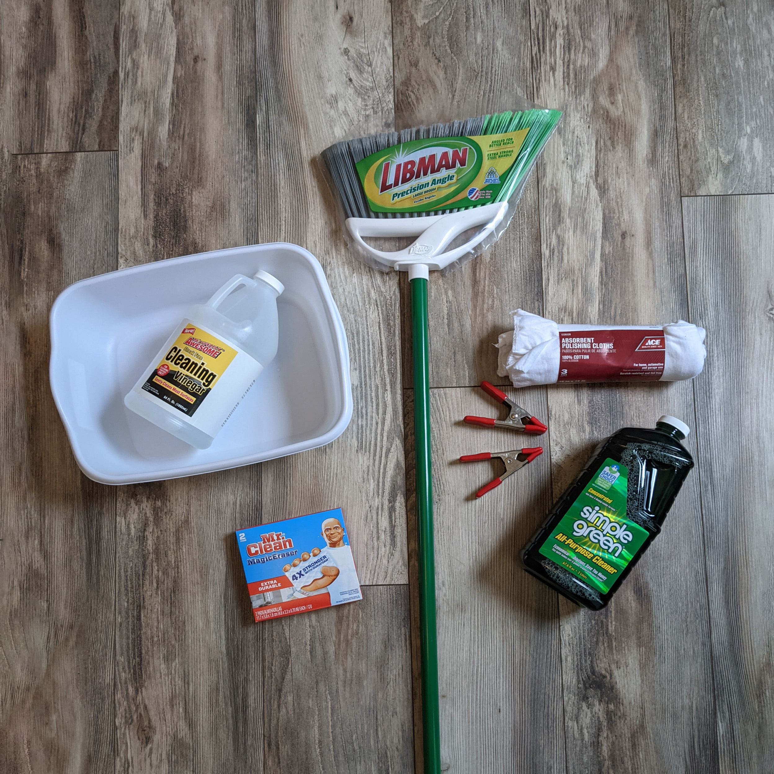 Tools for washing walls: dishpan, broom, towels, clamps, and cleanser.