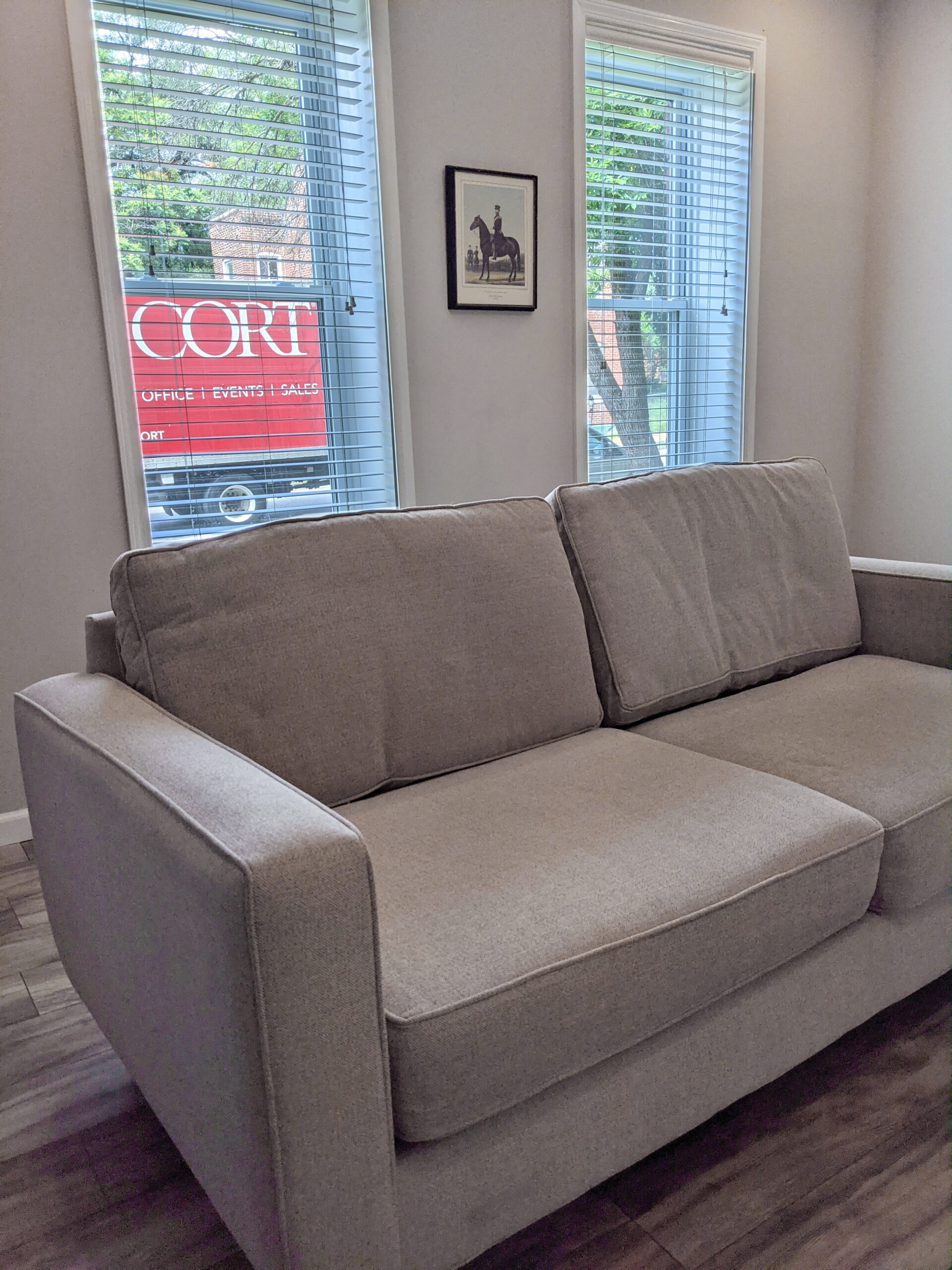 A used couch from the CORT outlet shortly after delivery, pictured with the CORT truck shown outside the window of the home.