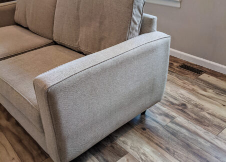 Closeup of a neutral colored sofa, showing an obviously used condition.