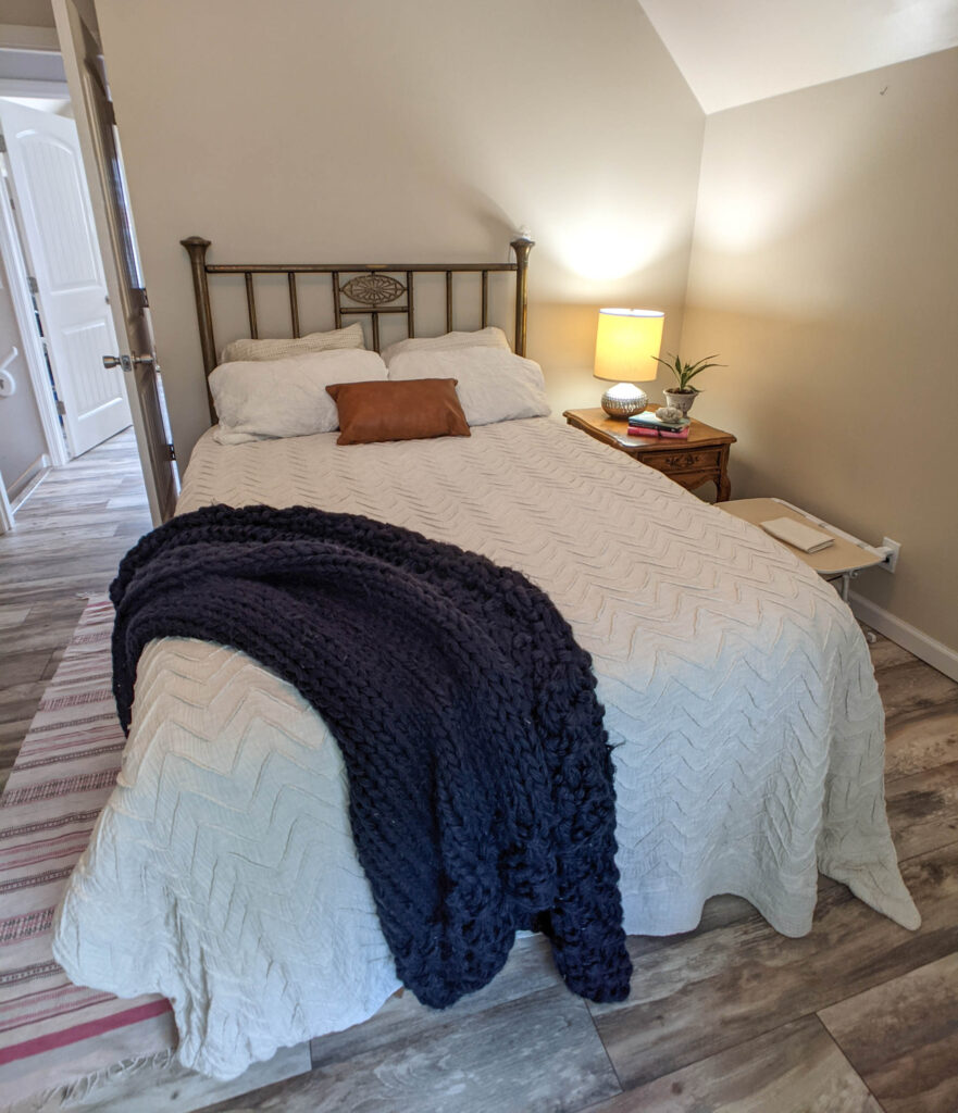 A bed with anthropology duvet and vintage headboard.