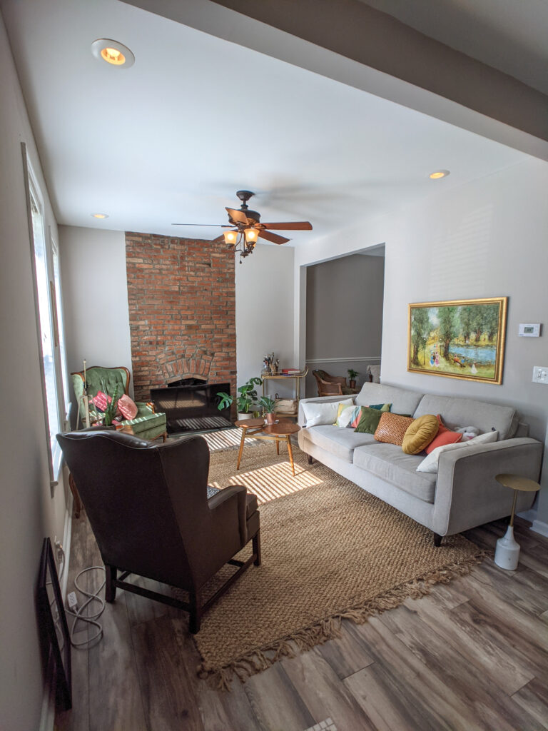 A living room with an exposed brick fireplace and a jute rug.