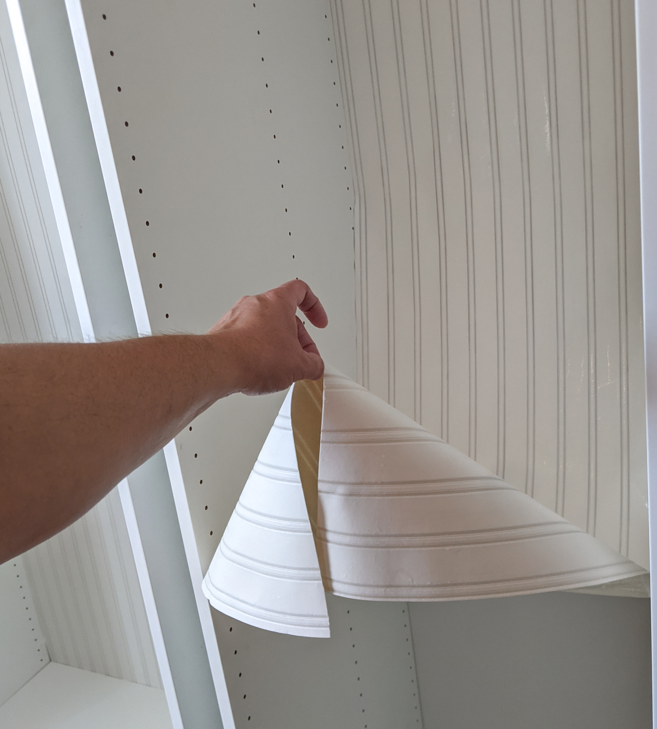 Bead board wallpaper being hung in an IKEA cabinet.