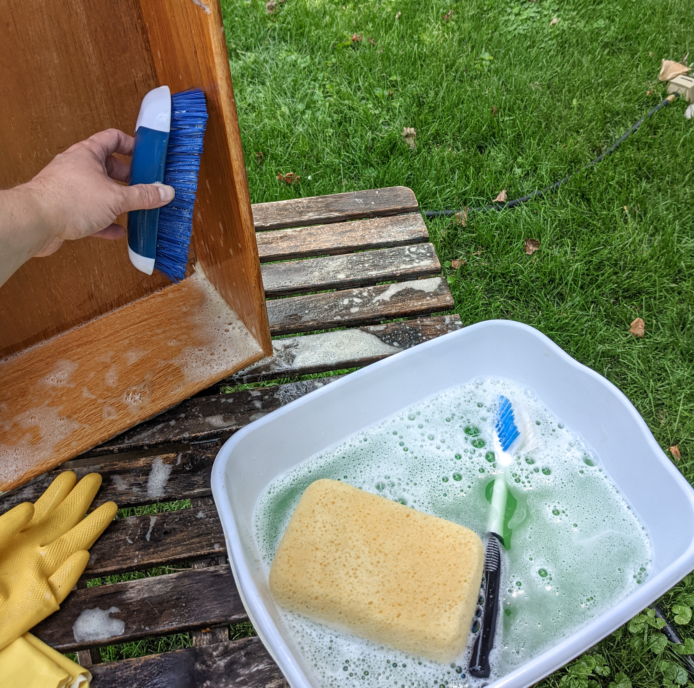 I hand holds a scrub brush as it scrubs the interior of the wood drawer.