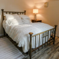 A modern adjustable bed and hybrid mattress with an antique bedframe.