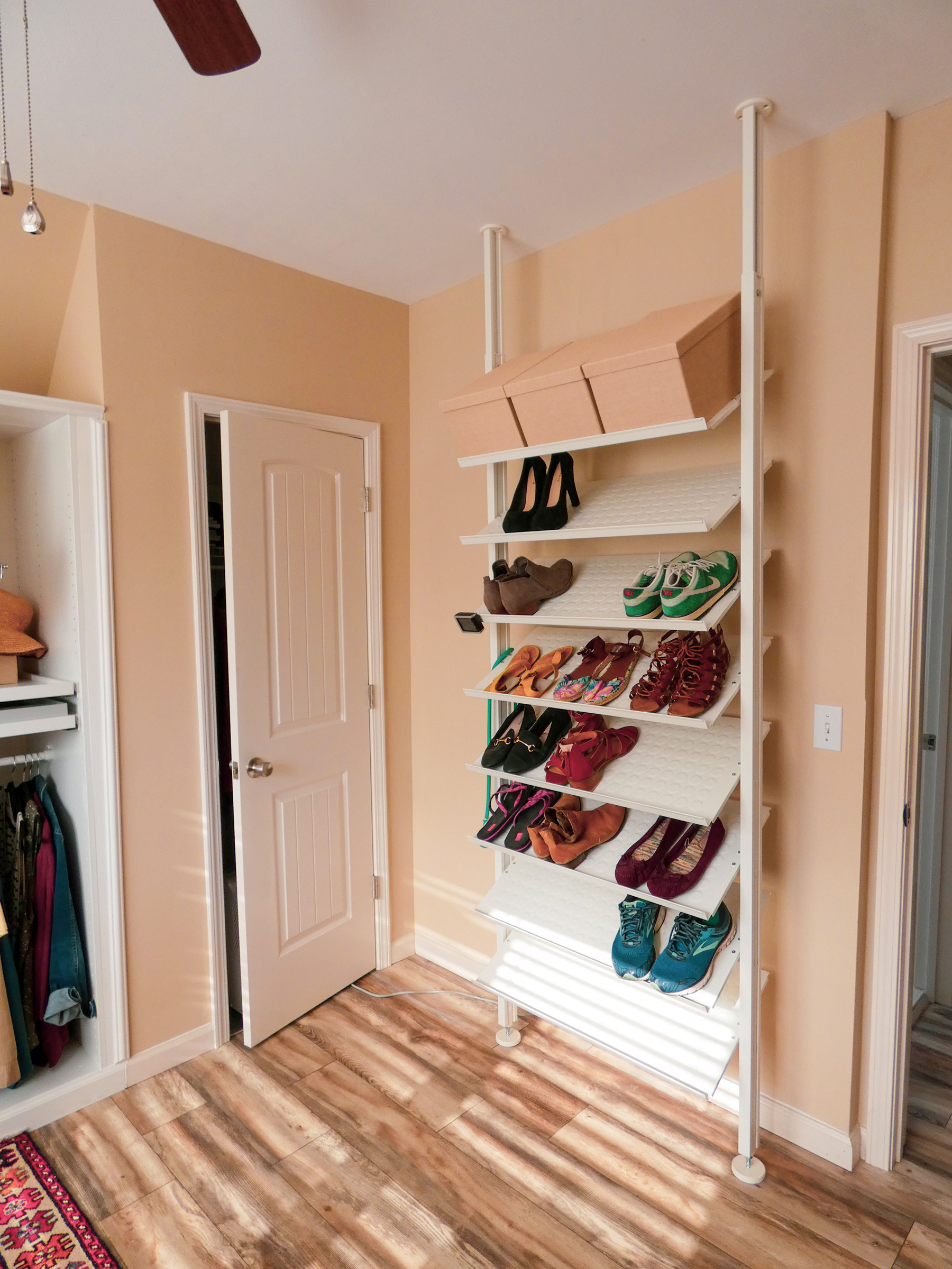 A floor to ceiling shelves built to hold shoes in a dressing room.