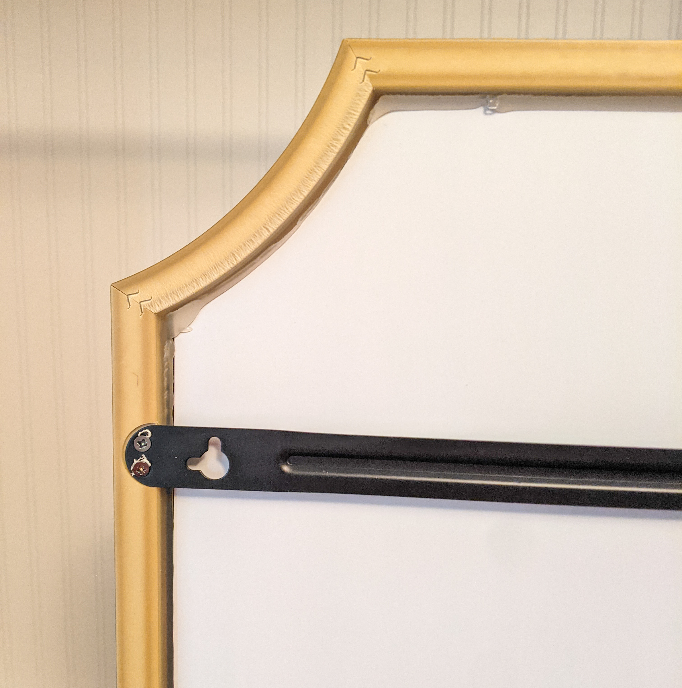 A close-up of the back side of the smear shows the support bars and hanging bracket, plus the back side of the frame and glue holding the mirror in the frame.