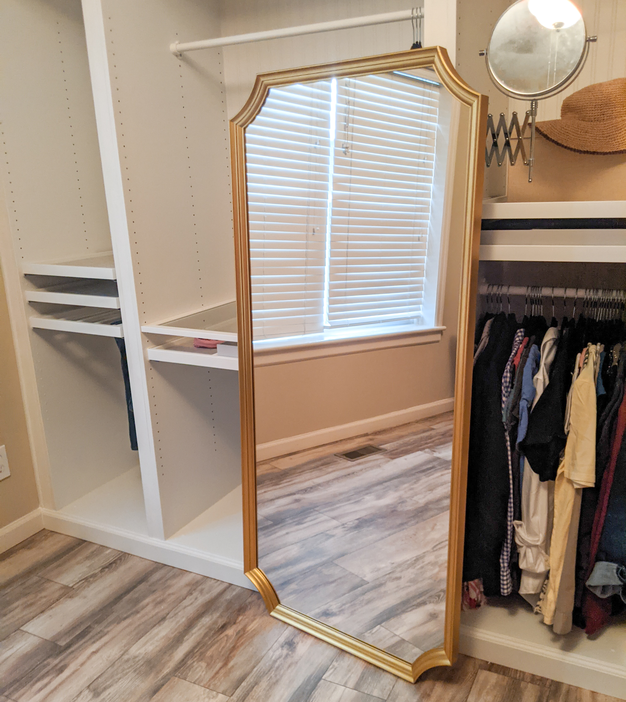 A large gold framed mirror in front of a half filled wardrobe.
