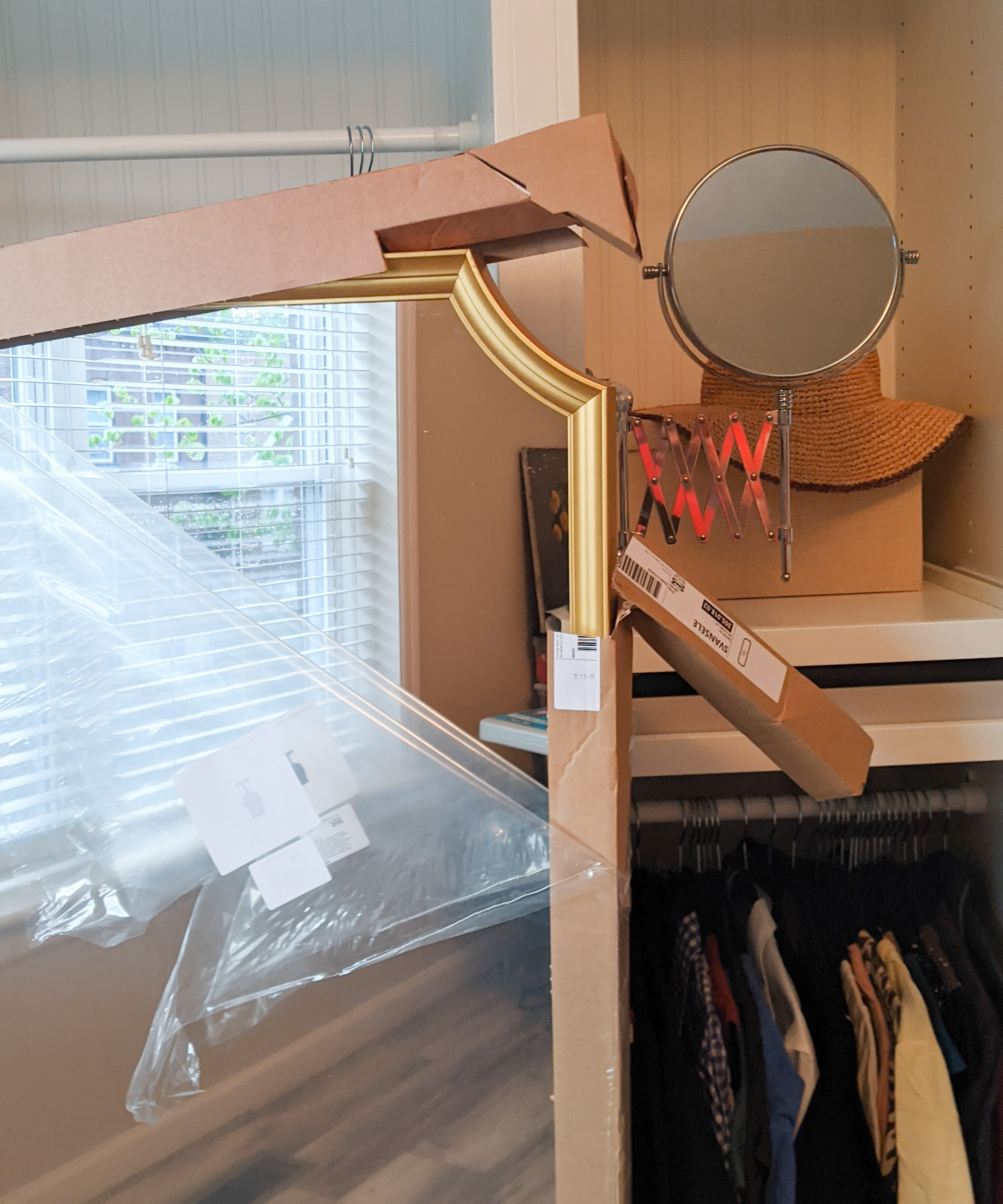 A partially unboxed ikea svansele mirror, with the gold frame peeking out of half removed cardboard packing.