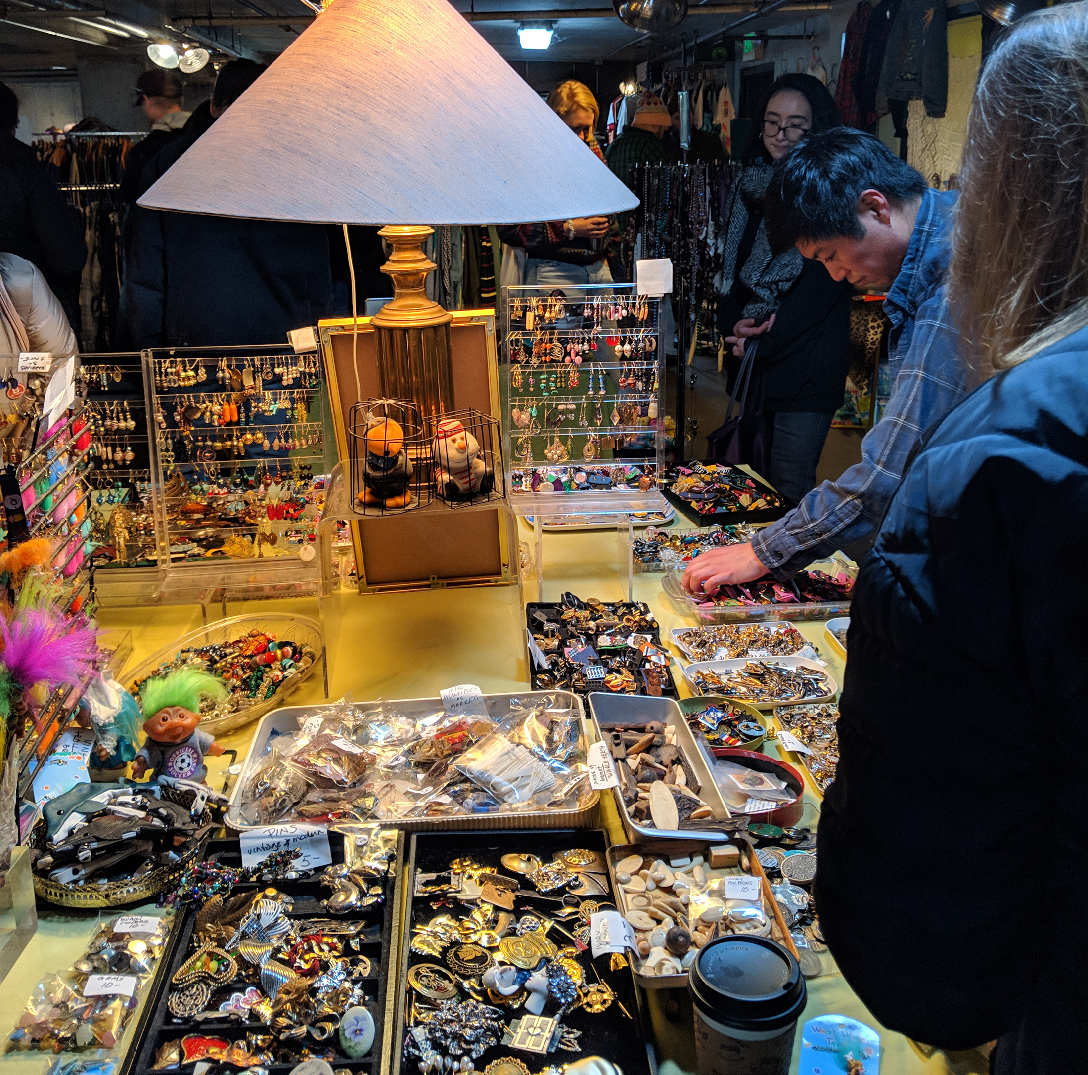 A flea market seller's goods spread out on a table by a lamp.