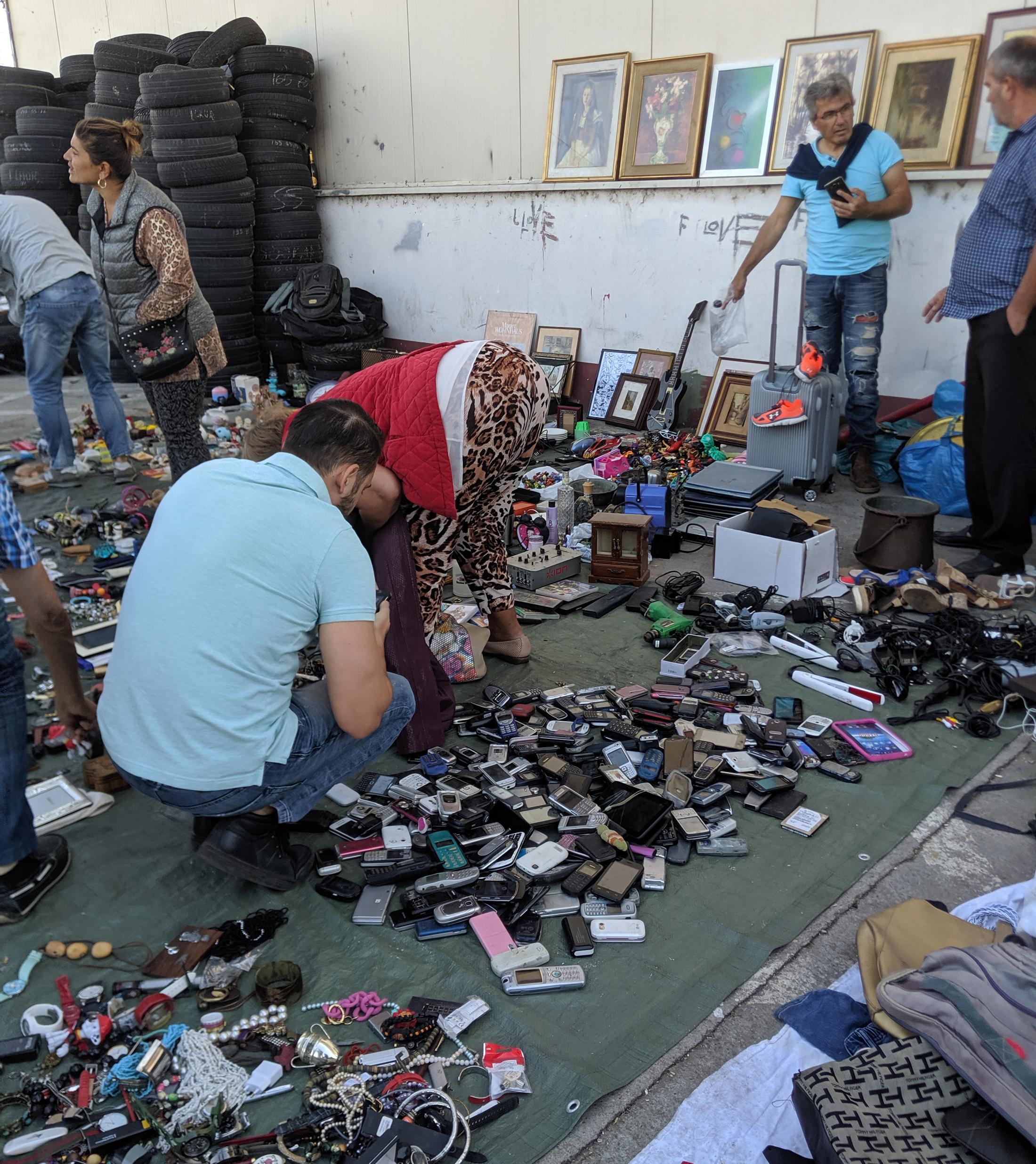 A flea market seller's goods spread out on a parking lot.