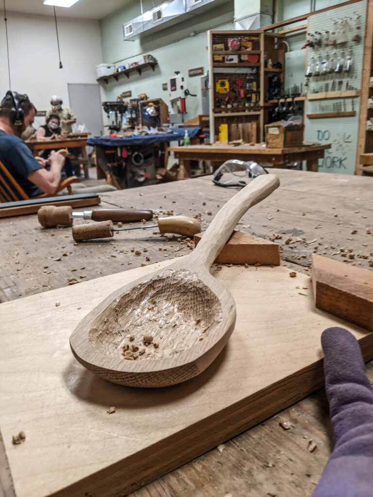 A handmade wooden spoon partially carved.