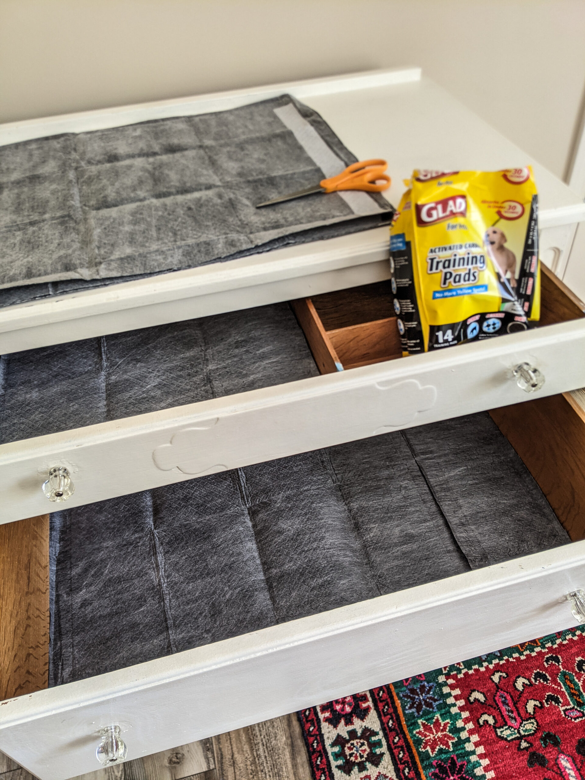 Wood dresser drawers lined with activated charcoal puppy pads.